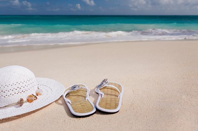 pantofle a klobouk na pláži